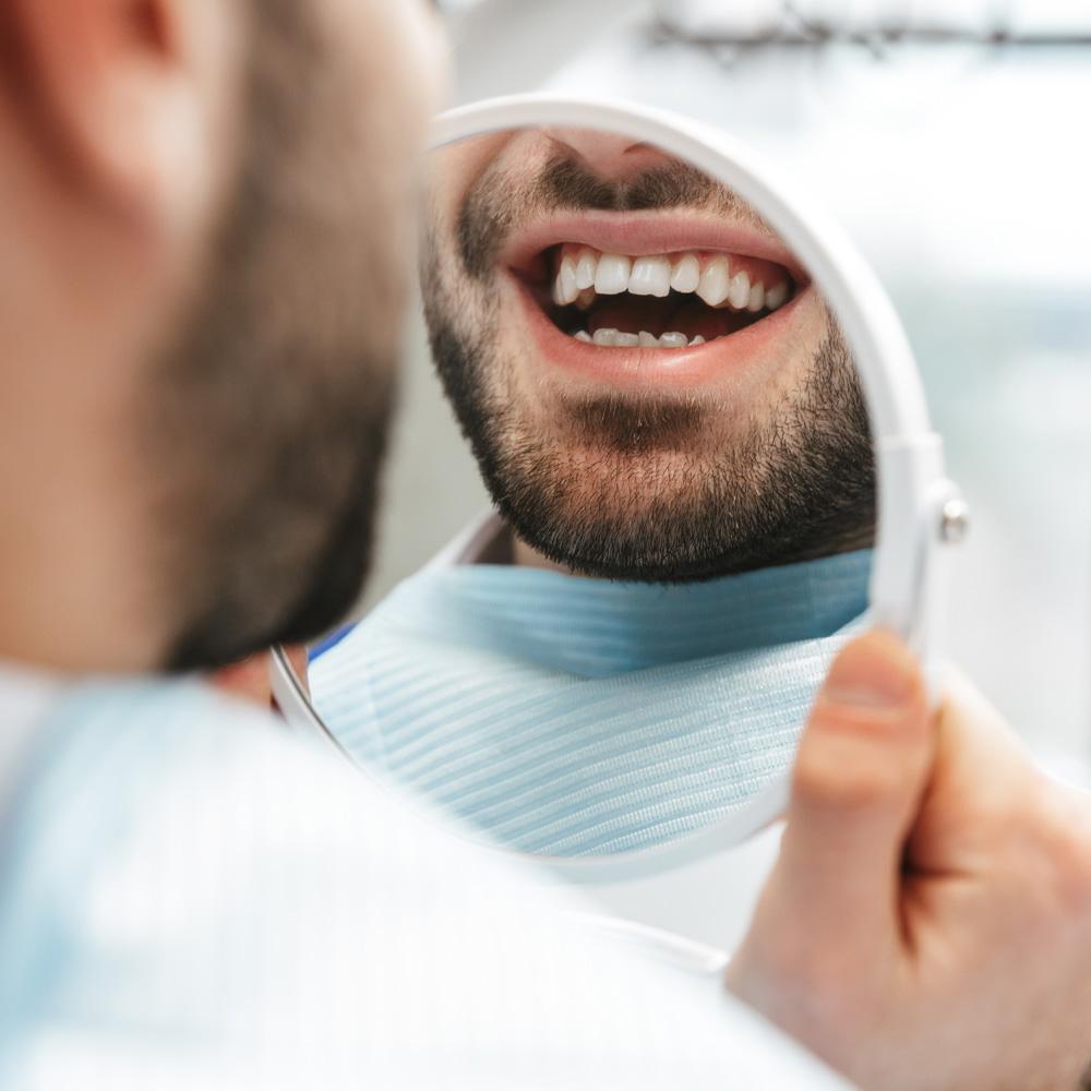 man admiring his new dental crown from dr zaborski
