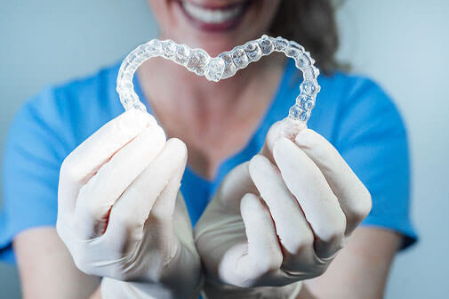 dentist lisa zaborski holding invisalign invisible braces