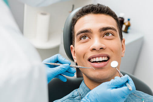 man getting a dental checkup and dr zaborki dental in shelby township mi